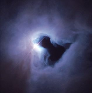 Photo of a luminous white spot surrounded by a grey and purple cloudy mass with a darker centre