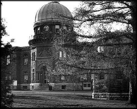 Black and white photo of a stone building with a domed roof, partially hidden by a tree.