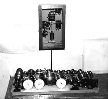 Black and white photo of a mechanism containing a base filled with cylindrical tubes connected to a rectangular box installed perpendicularly above the base.