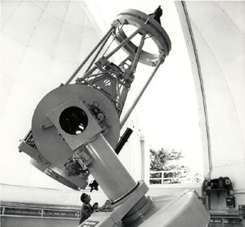 Black and white photo of a grey telescope pointing towards the sky through the opening of a white dome
