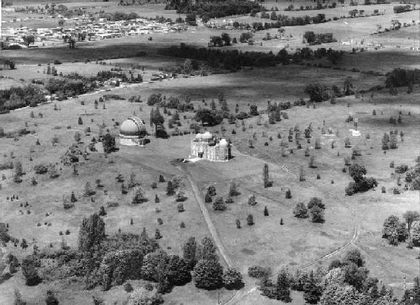 Black and white photo of two buildings with domes, with a scattering of young trees nearby and a residential neighbourhood at top left