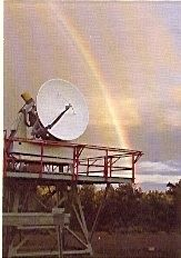 Colour photo of a white antenna installed on a metal structure with a rainbow in the background