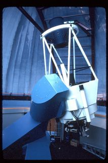 Photo of the blue and white structure of a telescope pointing towards the ceiling of a closed dome