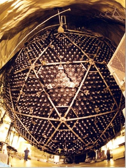 Colour photo of of a suspended brown sphere made of triangular metal components. Men are standing at each side of the sphere.