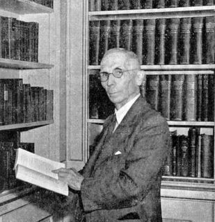 Black and white photo of a man in profile looking at the lens, holding a book in his hands and standing in front of a bookcase