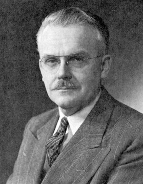 Black and white photo of a man with glasses and a mustache wearing a suit and tie