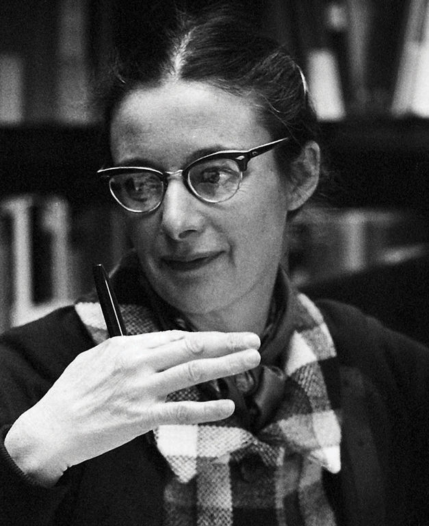 Black and white photo of a woman with glasses gesticulating in front of her shoulder with her right hand