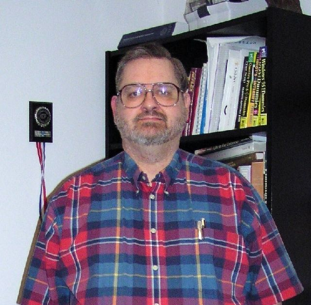 Colour photo of a man with glasses and a beard, wearing a checkered shirt, taken in front of a black bookcase and a white wall
