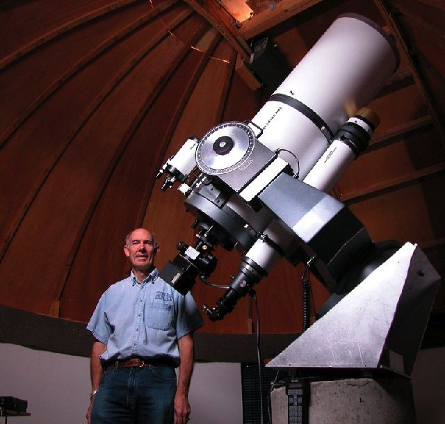 Low-angle photo of a man standing in front of a white telescope with a wooden dome in the background
