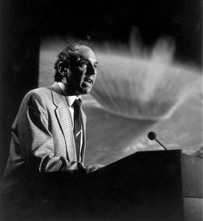 Black and white photo of a man wearing a suit, leaning on a lectern and speaking into a microphone with an explosion projected onscreen in the background