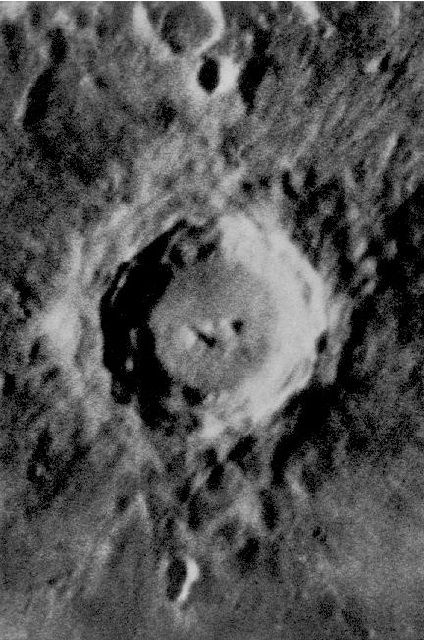 Black and white photo of a round crater with a raised, shaded centre surrounded by oval black and grey spots