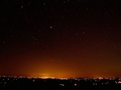 Photo of an orange glow on the horizon of a black starry sky, above urban lighting