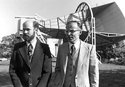 Black and white photo of two men in suits looking to their left and standing in front of a horizontal conical structure