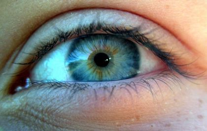 Close-up colour photo of a human eye with a blue iris tinged with yellow and brown.
