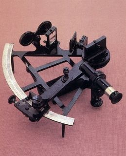 Colour photo of a black metal sextant with a curved, graduated section of one sixth of a circle, a scope and a lens