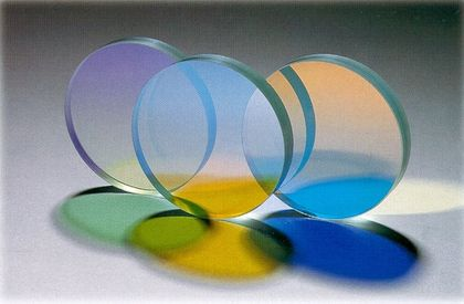 Three transparent violet, blue and orange discs containing ultraviolet filters aligned vertically through which light passes to create green, yellow and blue shadows.