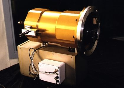 Photo of a camera made up of a tube-shaped gold-coloured metal structure connected to wires and installed on a rectangular wooden base