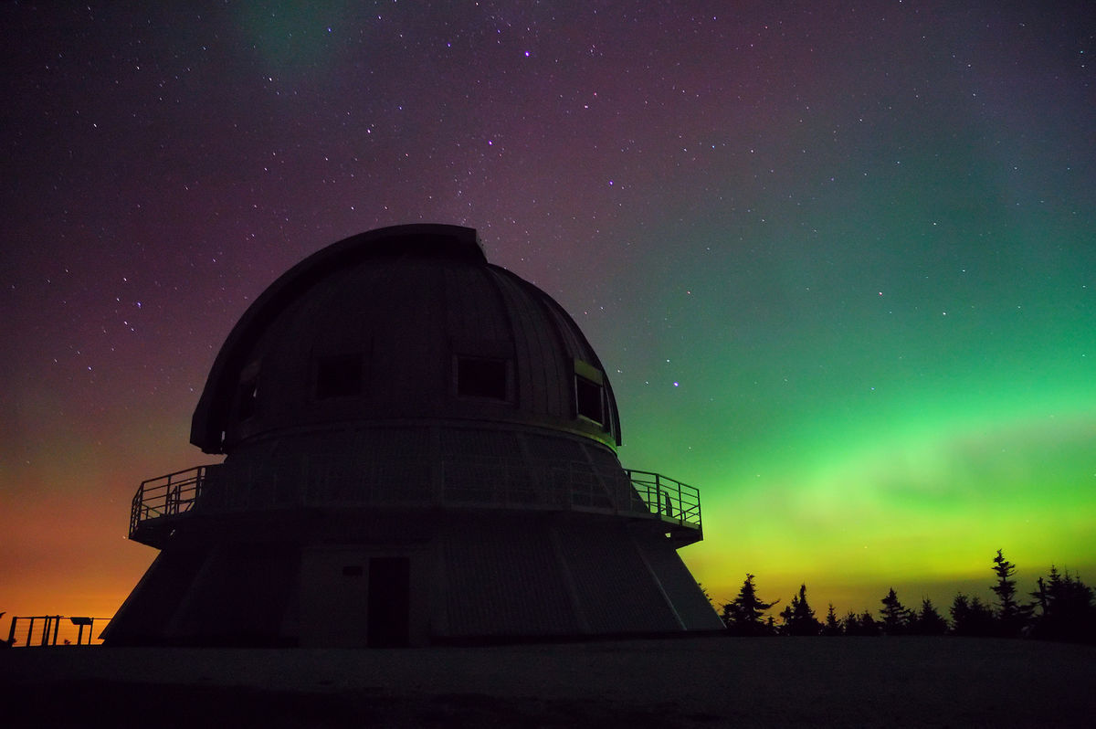 A backlit photo of a building with a dome facing a display of orange, pink and green Northern Lights