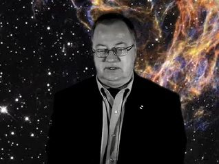 Black and white photo of a man wearing glasses and a suit against a star-filled black background with unearthly coloured filaments to the right