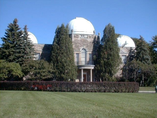 Colour photo of a grey building with three white domes, partially hidden by tall coniferous trees.