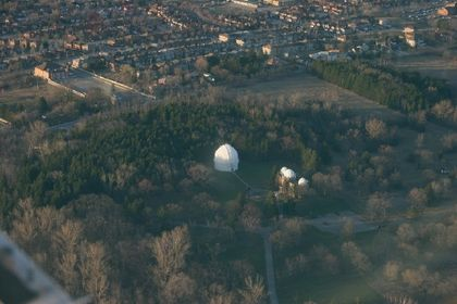 Aerial photo of two buildings with white domes, surrounded by a woodlot and bordered by a large residential neighbourhood