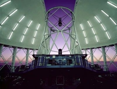 Photo taken inside an observatory where the base of the walls are raised, the white dome is open and a telescope is pointing towards a purple sky at dusk