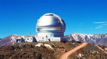 Photo of a silver-coloured observatory located on a hill with snow-covered mountains in the background