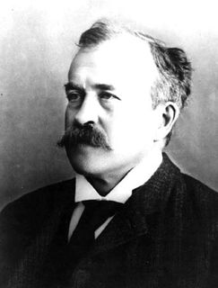 Black and white photo of a man with a long mustache wearing a black jacket and looking to his right