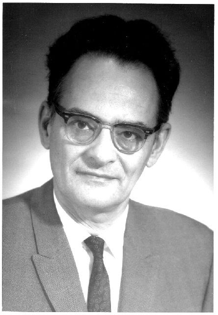 Black and white photo of a man with glasses and short black hair wearing a suit and tie
