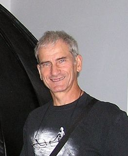 Colour photo of a man with short curly hair wearing a t-shirt and glasses hanging around his neck
