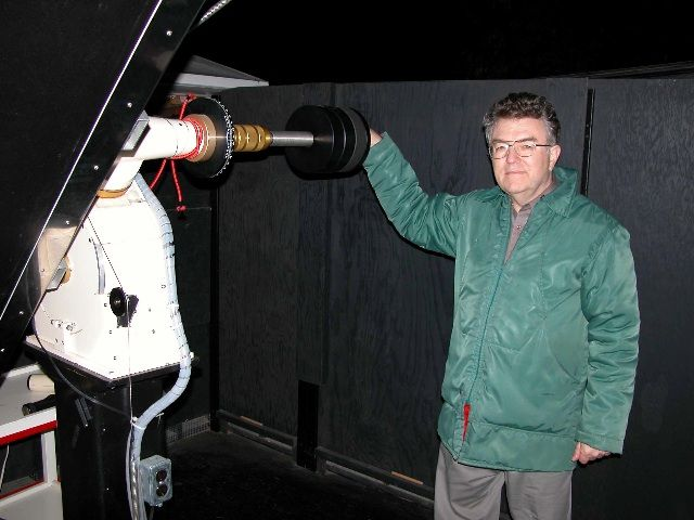 Photo of  a man wearing glasses and a green coat grasping a metal mechanism