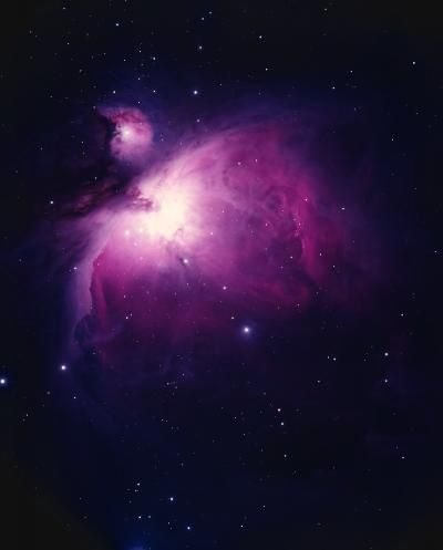 Photo of a nebula with a luminous centre, surrounded by a pink-tinged halo against a star-filled black background