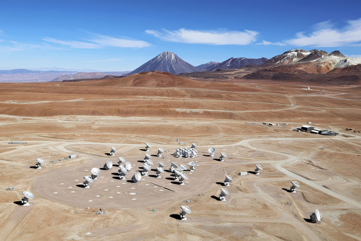 Photo of a group of white antennas aimed towards the sky and located in the desert with mountains and a blue sky on the horizon